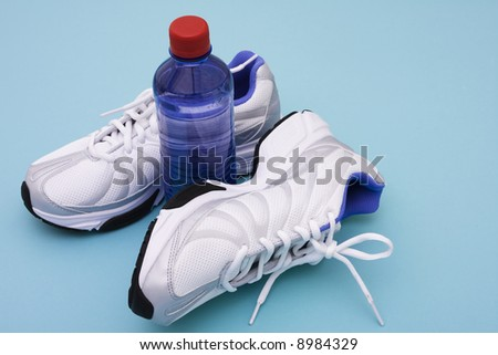 Sneakers with water bottle on blue background - stock photo