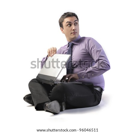 Sneaky businessman closing his laptop - stock photo