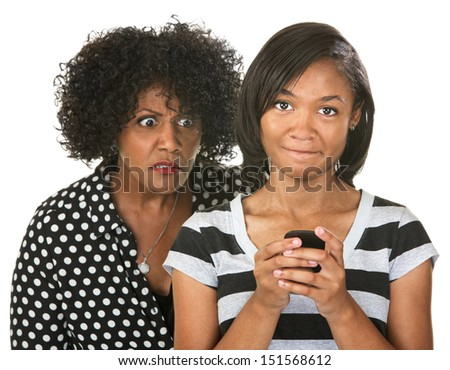 Sneering parent eavesdropping teenager using cell phone - stock photo