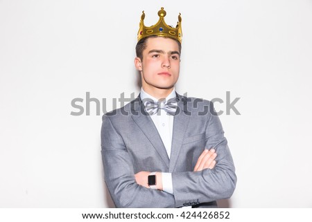 Sneering young handsome man wearing suit and crown keeping arms crossed and looking at camera while standing against white background - stock photo