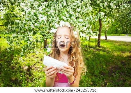 Sneezing girl. Child with a handkerchief. Allergy - stock photo