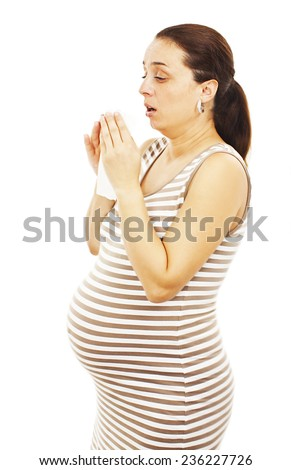 Sneezing pregnant woman. Isolated on white background  - stock photo