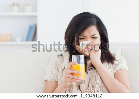 Sneezing woman drinking a glass of orange juice in a living room - stock photo