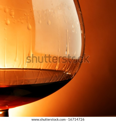 Snifter glass of cognac close-up over yellow background - stock photo
