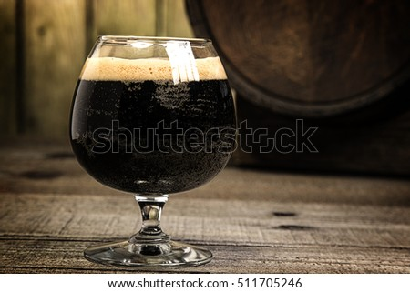 snifter glass of russian imperial stout craft beer with wood barrel in background