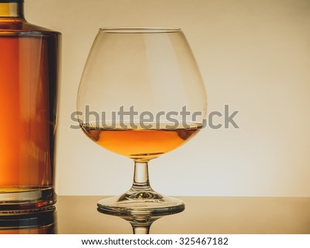 snifter of brandy in elegant typical cognac glass near bottle on table, warm style with space for text - stock photo