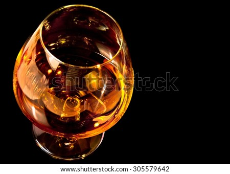snifter of brandy in elegant typical cognac glass on black background with space for text - stock photo