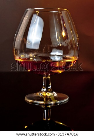 snifter of brandy in elegant typical cognac glass on dark background warm atmosphere