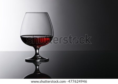 snifter of brandy on the reflective background