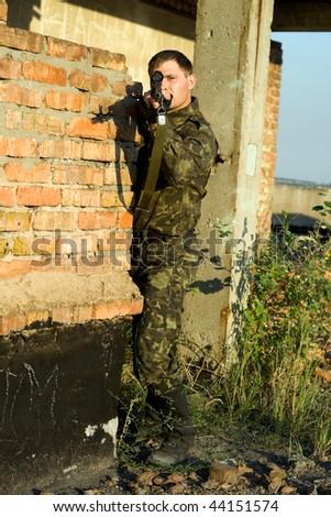 sniper in camouflage ambushing behind brick wall - stock photo