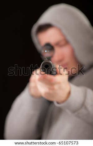 Sniper in hood aims at rifle optical sight - stock photo