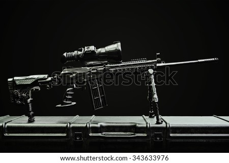 sniper rifle on the case on the dark background - stock photo