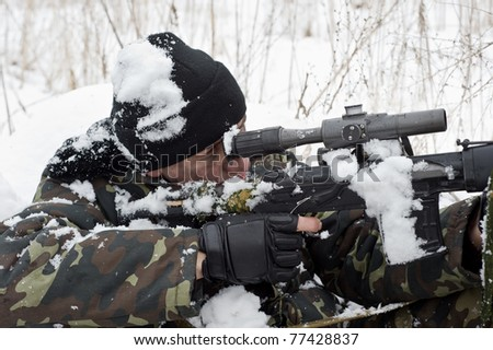 sniper rifle to the position.warrior in the winter forest.military action.commando. - stock photo