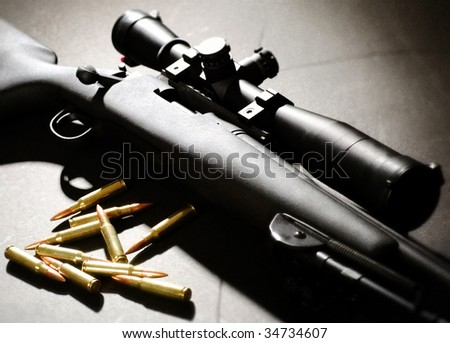 Sniper rifle with bullets and moody lighting - stock photo