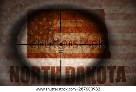 sniper scope aimed at the vintage american flag and north dakota state map - stock photo