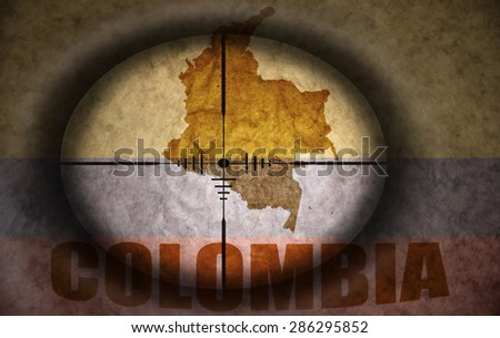 sniper scope aimed at the vintage colombian flag and map - stock photo