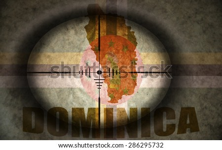 sniper scope aimed at the vintage dominica flag and map - stock photo