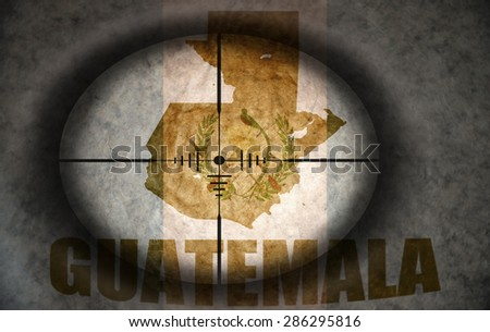 sniper scope aimed at the vintage guatemalan flag and map - stock photo