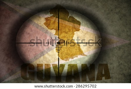 sniper scope aimed at the vintage guyanese flag and map - stock photo