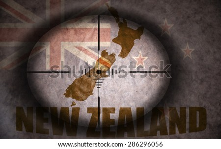 sniper scope aimed at the vintage new zealand flag and map - stock photo