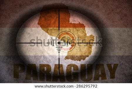 sniper scope aimed at the vintage paraguayan flag and map - stock photo