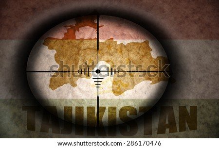 sniper scope aimed at the vintage tajikistan flag and map - stock photo