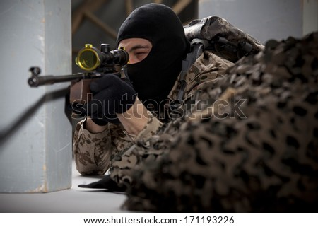 Sniper - soldier in camouflage and balaclava aiming with a sniper rifle - stock photo