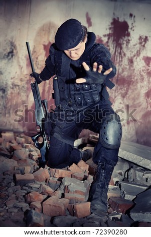 Sniper with the rifle in NATO uniform on the bloody wall background. - stock photo