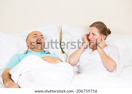 Snoring man. Couple in bed, man snoring and woman can not sleep, covering ears with hands for snore noise. Middle aged couple, attractive woman, caucasian man sleeping in bed at home. Face expressions - stock photo