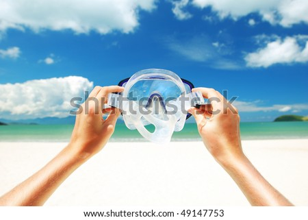 Snorkel equipment against beach and sky - stock photo