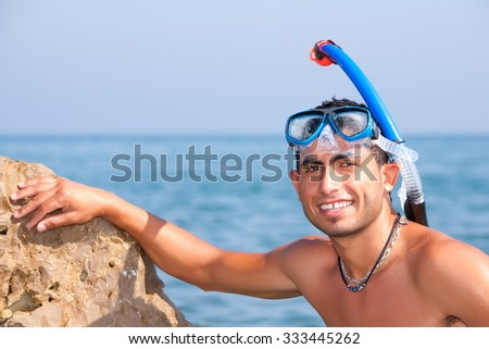 Snorkeler Resting On Shore With His Diving Equipment - stock photo