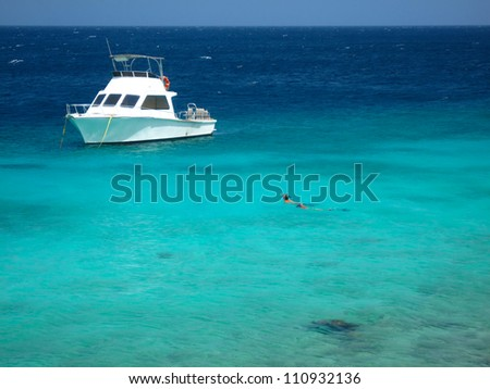 Snorkeling in Caribbean Sea with dive boat, Curacao, Netherlands Antilles, - stock photo