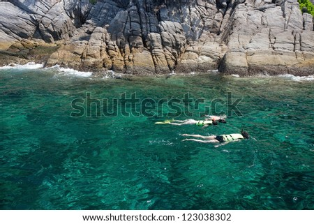 snorkeling in clean water over coral reef - stock photo