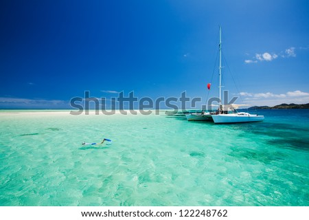 Snorkeling in shallow tropical water off the catamaran - stock photo