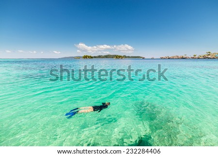 Snorkeling in the transparent water of the remote Togean Islands, Central Sulawesi, Indonesia. - stock photo