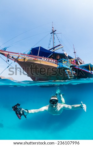 Snorkeller freedives below the surface in front of a traditional wooden boat - stock photo