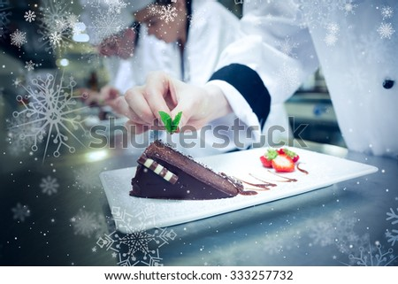 Snow against close up of chef putting mint leaf on chocolate cake - stock photo