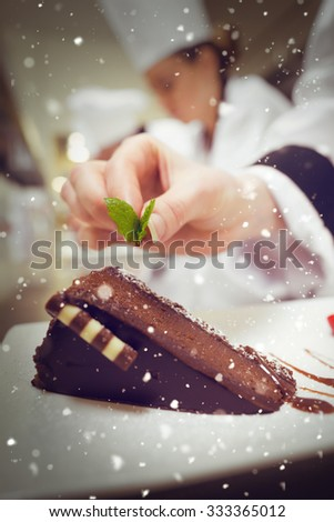 Snow against close up of chef putting mint leaf on chocolate dessert - stock photo