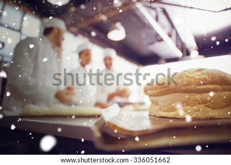 Snow against fresh bread with bakers behind him - stock photo