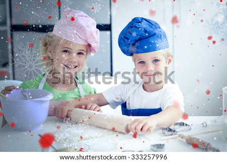 Snow against happy brother and sister preparing a dough standing in the kitchen - stock photo