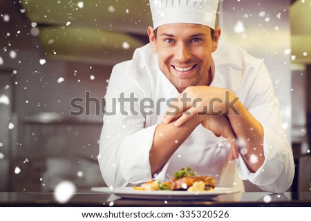 Snow against smiling male chef with cooked food in kitchen - stock photo