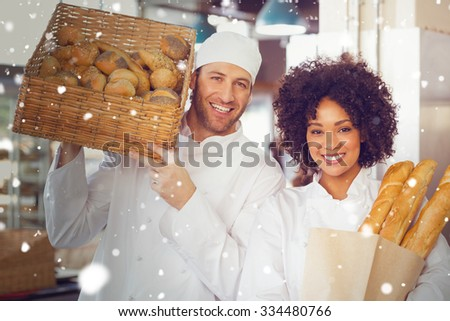 Snow against team of bakers smiling at camera - stock photo