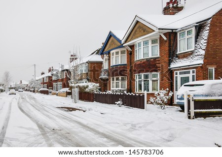 Snow and ice on an urban city road in the Winter - stock photo