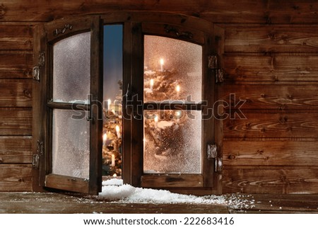 Snow at Open Vintage Wooden Christmas Window Pane, Captured with Christmas Lights Inside. - stock photo