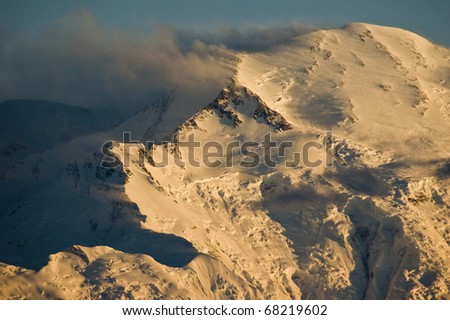 Snow blows off the top of Denali, otherwise known as Mount McKinley, in a fierce windstorm in Denali National Park, Alaska - stock photo