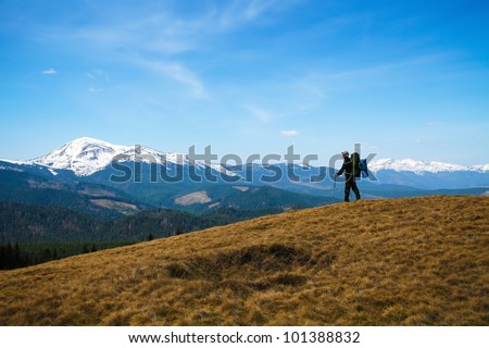 snow-capped Carpathian mountains and man with backpack on hill - stock photo