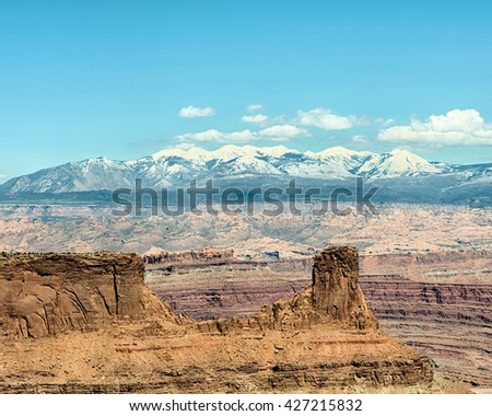 Snow-capped La Sal mountains rise above a butte on the East Rim Trail, in Dead Horse State Park, near Moab, Utah. - stock photo
