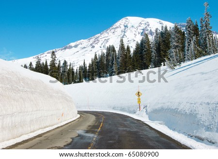 snow capped Mount Rainier and high walls of paved snow - stock photo