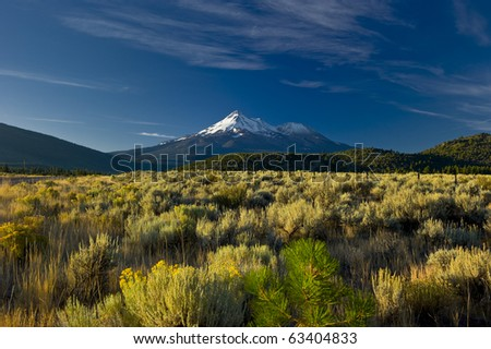 Snow capped Mount Shasta Volcano towers over the California landscape - stock photo