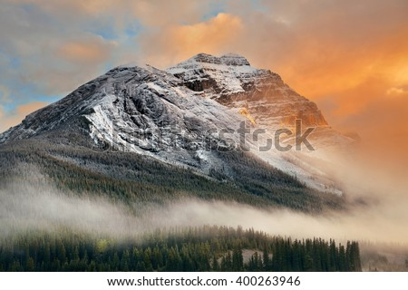 Snow capped mountain and fog at sunset in Yoho National Park in Canada - stock photo